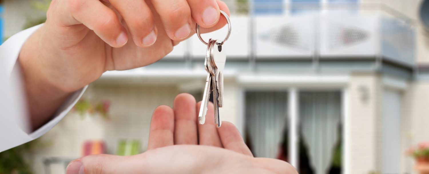 Close-up of real estate agent's hands giving keys to someone
