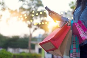 Woman holding shopping bags in pretty light